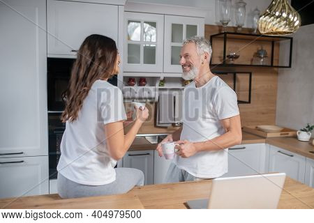 Couple Having Morning Coffee On Their Kitchen