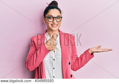 Beautiful middle eastern woman wearing business jacket and glasses showing palm hand and doing ok gesture with thumbs up, smiling happy and cheerful