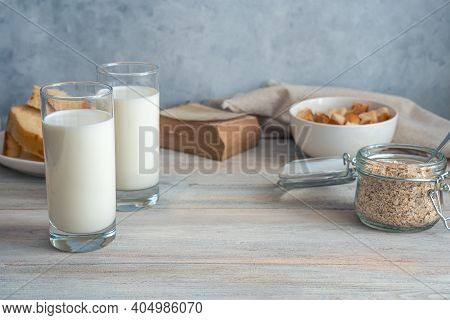 Grocery Background With Milk, Oatmeal And Bread On A Gray Background.