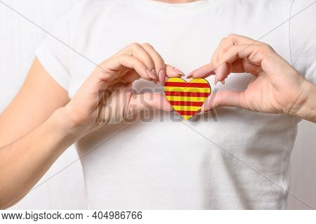 Love Catalonia. The Girl Holds On Her Chest A Heart In The Form Of The Official Flag Of Catalonia. C