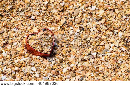 On A Seashell Beach, There Is A Heart-shaped Box Filled With Shell Fragments. There Is Free Space Fo