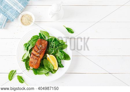 Salmon Fish Fillet Grilled And Fresh Spinach Salad On Plate For Lunch. Top View