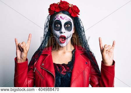 Woman wearing day of the dead costume doing rock and roll gesture with fingers afraid and shocked with surprise and amazed expression, fear and excited face.