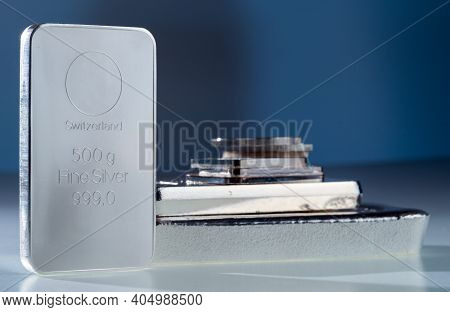 Silver Bullion. Cast And Minted Bars And Coins On A Blue Background. Selective Focus.