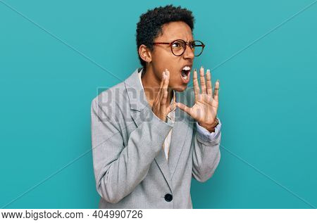 Young african american woman wearing business clothes shouting angry out loud with hands over mouth