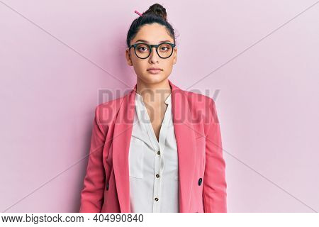 Beautiful middle eastern woman wearing business jacket and glasses relaxed with serious expression on face. simple and natural looking at the camera.