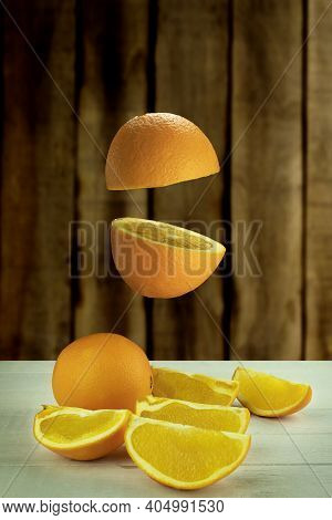 Fresh Orange Hovered In The Air On A Light Wooden Background. Levitation Of Orange On Wood Backgroun