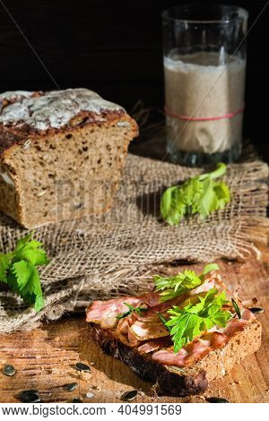 Sandwich With Bacon And Celery Leaves On A Slice Of Rye Bread Made From Leaven With Pumpkin Seeds. H