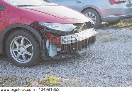 Side View Of A Red Car Without A Front Bumper. A Car From Which The Bumper Has Been Removed Or Disma