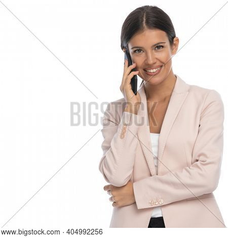 happy young businesswoman in pink jaket talking on the phone and smiling on white background in studio