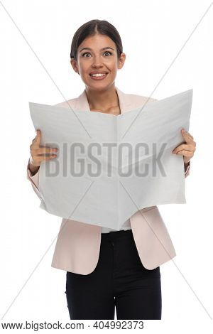 enthusiastic young businesswoman in pink jacket smiling and reading newspaper on white background in studio