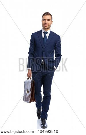 handsome bearded man in navy blue suit looking up, holding hand in pocket and holding suitcase walking isolated on white background in studio
