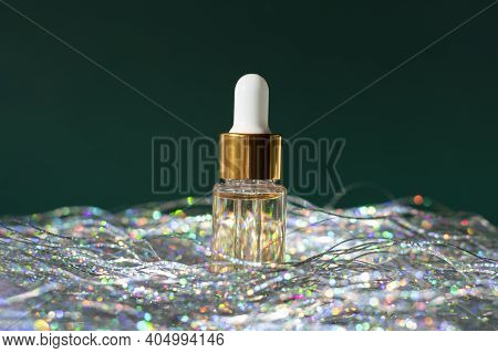 Gold Beauty Serum In A Pipette Bottle With Shiny Silver Tinsel On An Emerald Green Background
