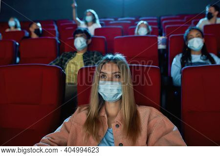 Young Woman Wearing Protective Face Masks While Watching Movie In Cinema Auditorium During Covid19 P