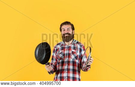 Man Holding Frying Pan.. Male Chef Kitchener Cooking. Hipster Checkered Shirt For Bearded Guy Cook.