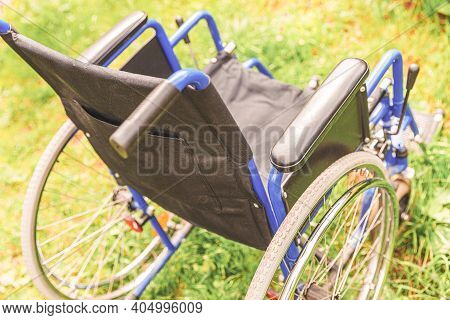 Empty Wheelchair Standing On Grass In Hospital Park Waiting For Patient Services. Invalid Chair For