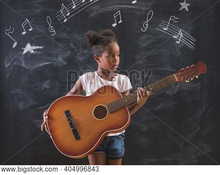 Beautiful Mixed Race Elementary School Girl Standing In Front Of A Chalkboard In Classroom, Playing