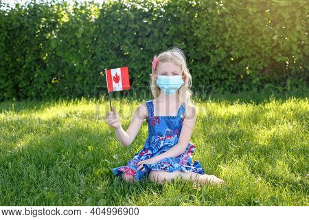 Caucasian Girl In Face Protective Mask Holding Waving Canadian Flag Outdoor. Child Kid In Sanitary M