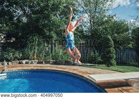 Girl Child Diving Jumping  In Water On Home Backyard Pool. Funny Cute Kid Enjoying And Having Fun In