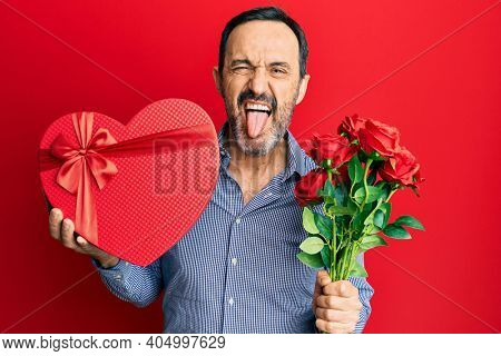 Middle age hispanic man holding valentine day gift and flowers sticking tongue out happy with funny expression.