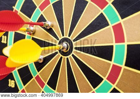 Closeup Of A Dartboard With Yellow And Red Magnetic Darts. Dart In Bulls Eye Of Dartboard Concept Fo