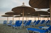 Deck chairs and bamboo umbrellas on a beach in Nei Pori Greece poster