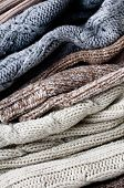 Texture of warm winter knitted sweaters on a white background. poster