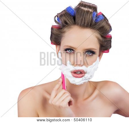 Delightful model in hair curlers posing with razor on white background