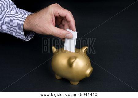 Putting Slip Of Paper In Piggy Bank