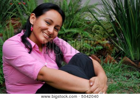 Beautiful Hispanic Woman Sitting Outside In The Grass