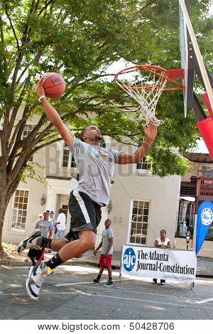 Man Attempts Slam Dunk During Outdoor Street Basketball Tournament