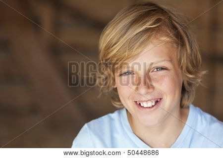 Young happy smiling blond boy child aged about twelve or early teenager