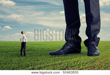 small businessman looking at his big boss. photo on green field