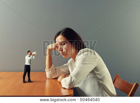 small man urge on tired businesswoman