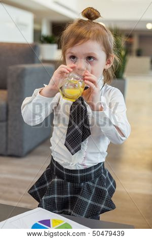 A little girl in a business clothes drinking juice in the business center