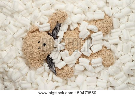Teddy bear laying in packing peanuts