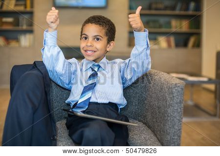 Little boy in a business suit with the tablet sitting in a chair in a business center and making a thumbs up