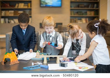 Four little children in business dress playing with toys on the table, one boy uses a puncher and girls play with a calculator
