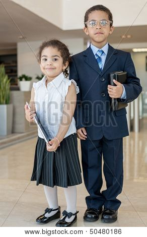Young children in business clothes in the business center with communication devices, vertical photo.