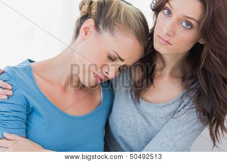 Woman consoling her upset friend and looking at camera