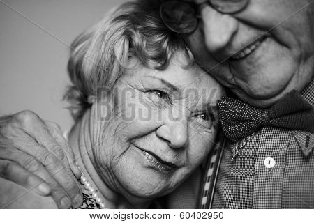 Black-and-white image of senior female being embraced by her husband poster