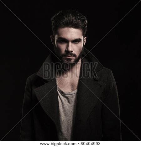 cool unshaved fashion model smiling at the camera on dark studio background