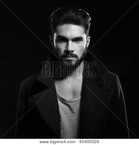 black and white portrait of a fashion man with beard wearing a long coat