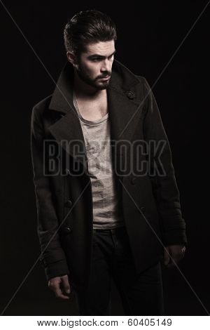 side view of a young casual fashion man in long coat looking away on dark studio background