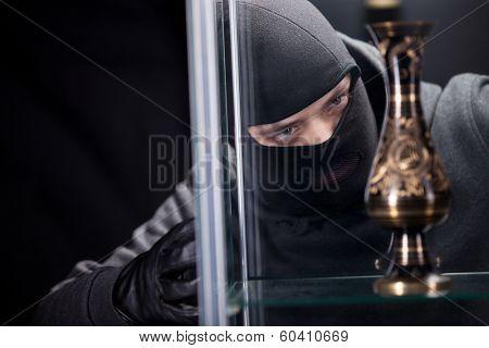 Angry burglar wearing black woollen mask, considering vase over black