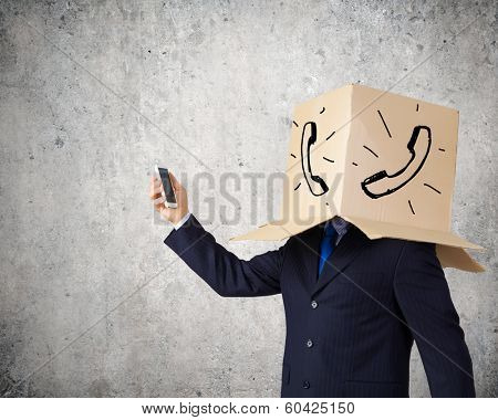 Businessman using mobile phone wearing carton box on head