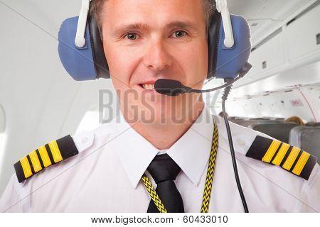 Pilot wearing uniform with epauletes, inside airliner
