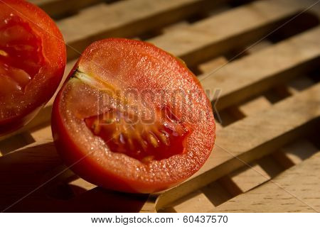 two sliced tomates on a wooded plate