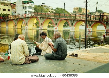 UDAIPUR - SEPT 20 2012:  Four man playing cards on the side of the Pichola lake at Udaipur also called