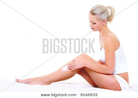 Woman Sitting On Bed  Applying Moisturizer Cream On Her Slim Legs